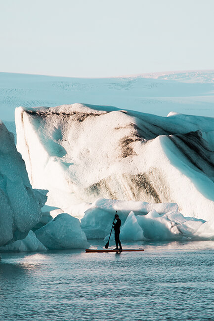 Travel prints for sale by Shilpa Iyer Photography of a person paddle boarding in Jokulsarlon Lagoon