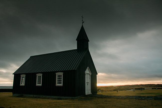 Black church of Budir in Iceland during a dark and stormy morning