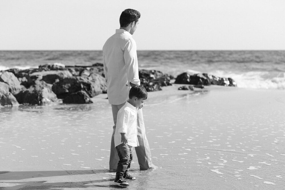 Black and Image of Father and Son during Family Photography session walking along beach in Sea Bright, NJ